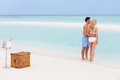 Couple on beach with luxury champagne picnic smiling Royalty Free Stock Photography