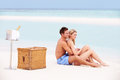 Couple on beach with luxury champagne picnic smiling Stock Image