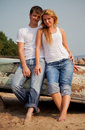 Couple on a beach near old boat Stock Photography