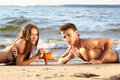 Couple at the beach outdoor portrait of beautiful romantic of topless girl and muscular guy in jeans laying face to face with Stock Image