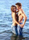 Couple at the beach outdoor portrait of beautiful romantic of topless girl and muscular guy in jeans posing in sea waters Stock Photo