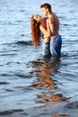 Couple at the beach outdoor portrait of beautiful romantic of topless girl and muscular guy in jeans posing in sea waters Royalty Free Stock Photo