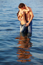 Couple at the beach outdoor portrait of beautiful romantic of topless girl and muscular guy in jeans posing in sea waters Stock Photos