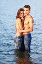 Couple at the beach outdoor portrait of beautiful romantic of topless girl and muscular guy in jeans posing in sea waters Stock Images