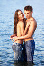 Couple at the beach outdoor portrait of beautiful romantic of topless girl and muscular guy in jeans posing in sea waters Stock Image