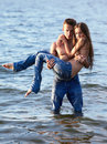 Couple at the beach outdoor portrait of beautiful romantic of topless girl and muscular guy in jeans posing in sea waters guy Royalty Free Stock Photos