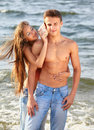 Couple at the beach outdoor portrait of beautiful topless girl putting shell to muscular guy s ear Royalty Free Stock Photos
