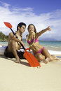 Couple on the beach with paddleboards their paddle boards Stock Photos