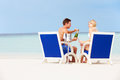 Couple on beach relaxing in chairs and drinking champagne smiling Royalty Free Stock Photo