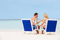 Couple on beach relaxing in chairs and drinking champagne smiling Royalty Free Stock Photos