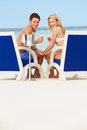 Couple on beach relaxing in chairs and drinking champagne smiling at camera Royalty Free Stock Photos