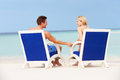 Couple on beach relaxing in chairs holding hands Royalty Free Stock Photos