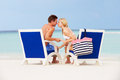Couple on beach relaxing in chairs smiling Stock Photography