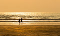 Couple on beach a in romantic mood walking a during sunset waves in the background and sandy summer warm orange sky model Stock Photography