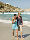 A couple on the beach sunny walking by waves Stock Image