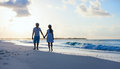 Couple on beach at sunset romantic walking along a Royalty Free Stock Photos
