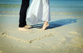 Couple on the beach with symbol of heart sand Stock Photography