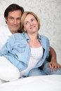 Couple on bed sat together Royalty Free Stock Images