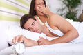 Couple in bed waking up the men switches off the alarm clock Stock Photography