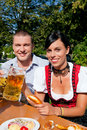 Couple in beer garden eating and drinking Royalty Free Stock Photo