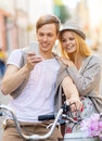 Couple with bicycles in the city summer holidays bikes love relationship navigation gps and dating concept and smartphone Royalty Free Stock Photo