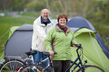 Couple with bicycles standing against tent in forest portrait of happy Royalty Free Stock Photo