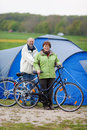 Couple with bicycles standing against tent portrait of happy Stock Photos