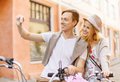 Couple with bicycles taking photo with camera summer holidays travel vacation tourism and dating concept travelling picture Stock Images