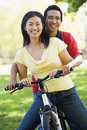 Couple on a bike outdoors smiling Stock Image