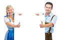 Couple with a billboard in traditional bavarian tracht stand behind and show thumbs Royalty Free Stock Photo