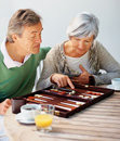 Couple at the breakfast table playing backgammon Royalty Free Stock Photo