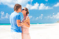 Couple in bright clothes on tropical beach kissing Stock Photo
