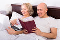 Couple burring with laptop mature caucasian in bedroom interior Stock Images