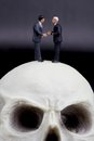 Couple of businessmen in miniature handshaking over a skull Royalty Free Stock Photo