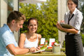 Couple at cafe ordering from menu waitress Stock Photo