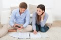 Couple calculating budget at home full length of in living room Royalty Free Stock Images