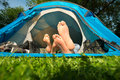 Couple on camping feet of a young lying in a tent Stock Images
