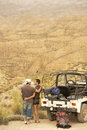 Couple by car looking at desert from cliff rear view of affectionate standing four wheel drive Royalty Free Stock Image