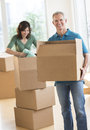 Couple with cardboard boxes in house mature their new Stock Photography