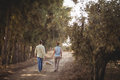 Couple carrying basket while walking on dirt road at farm Royalty Free Stock Photo
