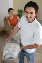Couple carrying carpet Royalty Free Stock Photo