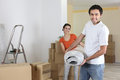 Couple carrying carpet into home Royalty Free Stock Image