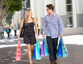 Couple carrying shopping bags on city street smiling Royalty Free Stock Photography