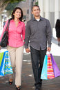 Couple carrying shopping bags on city street smiling Royalty Free Stock Photo