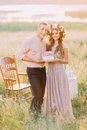 Couple celebrating at picnic, young man and woman holding cake decorated with pink flowers, wooden chairs on background Royalty Free Stock Photo