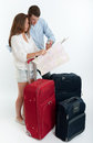 Couple checking destination map young surrounded by baggage a Royalty Free Stock Photos