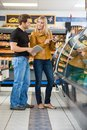 Couple checking ingredients of product at with digital tablet butcher s shop Royalty Free Stock Images