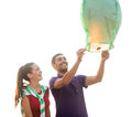 Couple with chinese sky lanterns on the beach summer holidays vacation happy people concept Stock Photos
