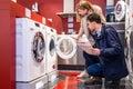 Couple Choosing Washing Machine At Hypermarket Royalty Free Stock Photo