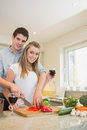 Couple chopping peppers and drinking wine in kitchen Stock Photo